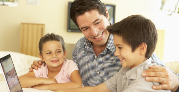 Hispanic Father And Children Using Computer At Home